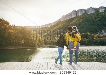 Family spending time together by the lake in autumn. Mom with her daughters standing and looking at the landscape. Fall weekend in the open air.