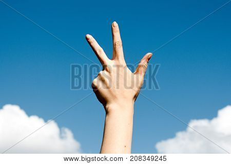 Three finger salute hand gesture on blue sky background