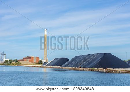 industrial site by a canal or river with storage site covered piles chimney