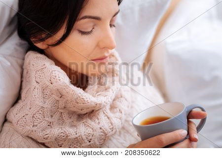 Strong tea. Ill exhausted young woman sitting with her eyes closed while drinking strong black tea
