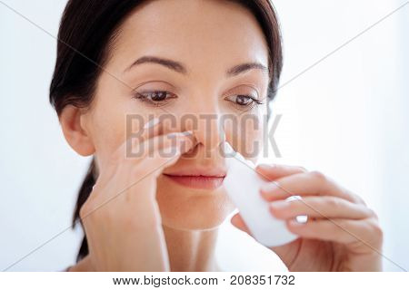 Blocked nose. Cheerful kind smiling woman curing her blocked nose with a help of special useful nasal drops