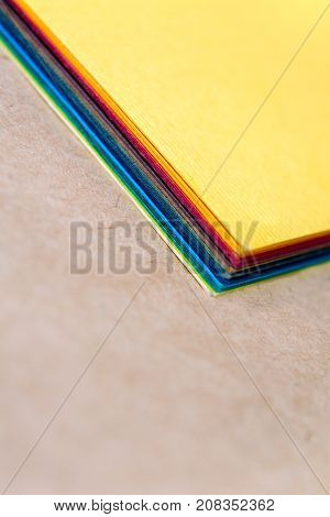 Stack of colorful paper. Blurring background. The corners of sheets of paper close-up. Back to school. Bright natural background.