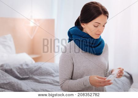 Curious woman. Calm thoughtful woman holding an empty pillbox while sitting in her room