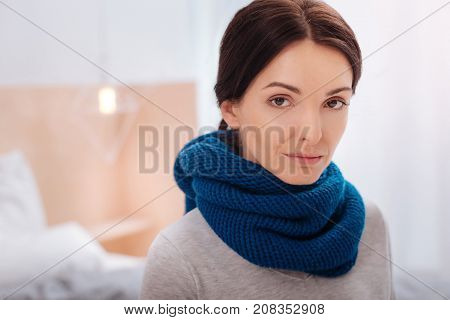 Serious look. Strict glance of a calm thoughtful young woman wearing a dark blue scarf