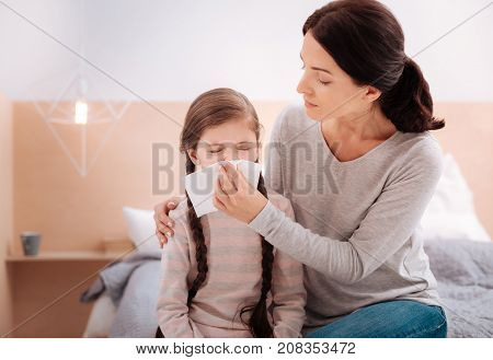 Sitting together. Ill sneezing girl sitting on the bed together with her kind attentive loving mother