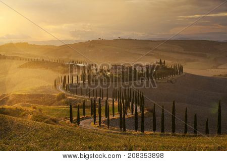 Tuscany, Italy - September 27, 2017: Lonely farmhouse with cypress trees and rolling hills in autumn sunset near Crete Senesi, Tuscany, Italy.