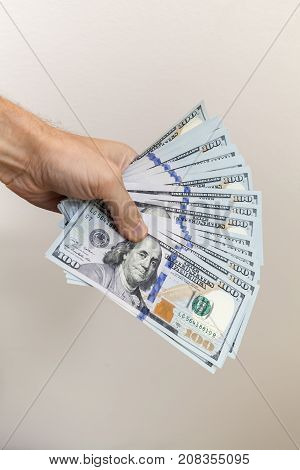 Fan Of 100 Dollars Notes In Male Hand Over Gray