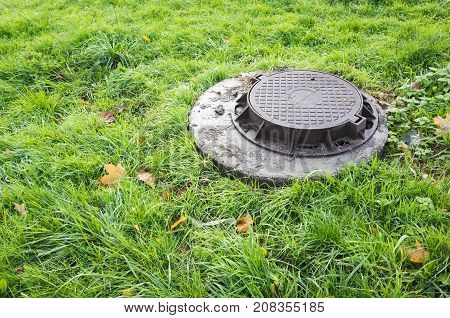 Round Sewer Manhole Cover In Green Lawn