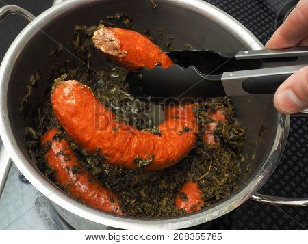 Cooked kale with tasty smoked sausages in a stainless steel pot