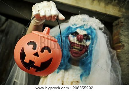 closeup of a scary evil clown wearing a bride dress, with a veil and a diadem, at the door of a scary house holding a treat basket in the shape of a jack-o-lantern