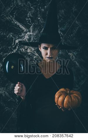 Halloween Witch holding a pumpkin and a black air balloon. woman dressed like a fairy witch