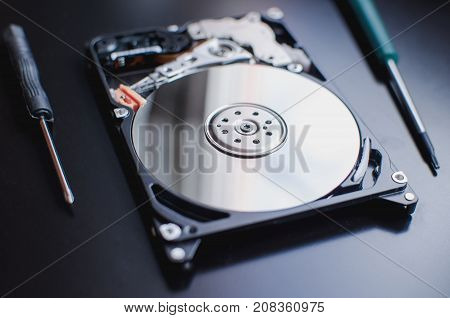 Repair of the dismantled hard drive. Hdd with mirror effect. Screwdrivers for computer repair.