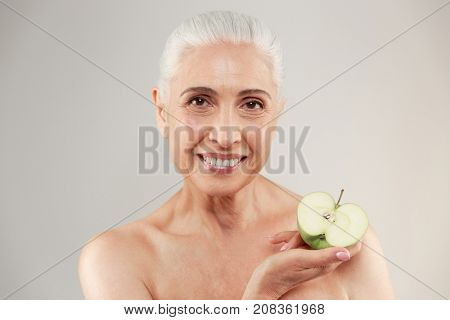 Beauty portrait of a smiling half naked elderly woman holding sliced green apple and looking at camera isolated over white background