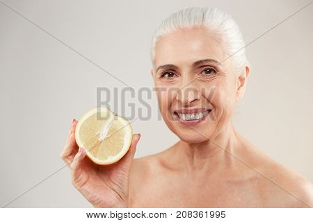 Beauty portrait of a happy half naked elderly woman showing a sliced orange and looking at camera isolated over white background