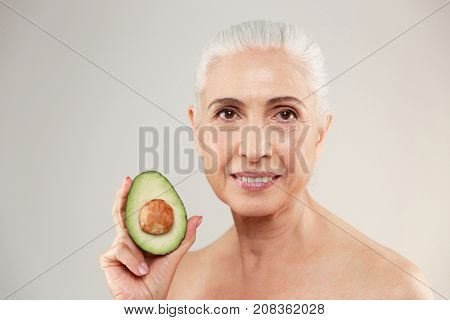 Beauty portrait of a smiling half naked elderly woman showing an avocado and looking at camera isolated over white background