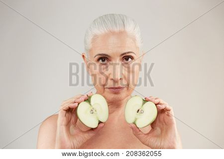 Beauty portrait of an attractive half naked elderly woman holding two slices of green apples and looking at camera isolated over white background