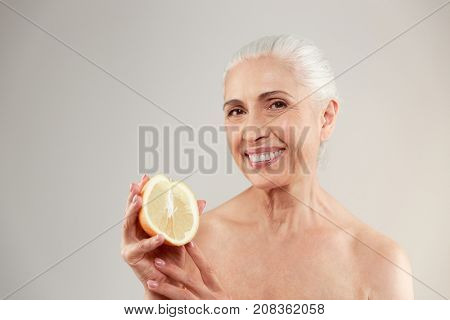 Beauty portrait of a smiling half naked elderly woman showing a sliced orange and looking at camera isolated over white background