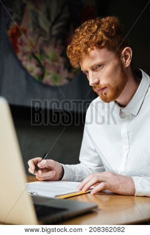 Portrait of thinking young readhead man looking at laptop at workplace