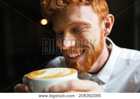 Close-up portrait of smiling curly readhead bearded man tasting coffee in cup