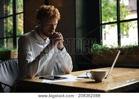 Young readhead bearded man holding hands together and thinking while sitting in the cafe