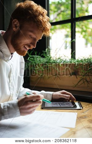 Side view of happy readhead bearded worker in white shirt, reading papers