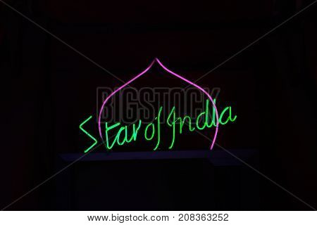 SAN PAWL, MALTA - APRIL 2, 2017 - Green and pink neon Star of India restaurant sign against a black background San Pawl Malta Europe, April 2, 2017.