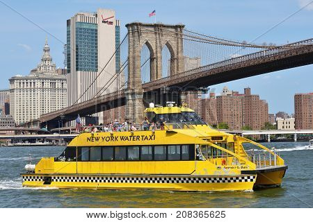 NEW YORK CITY - AUG. 27: boat under Brooklyn Bridge on August 27 2017 in New York City NY. The Brooklyn Bridge is one of the oldest bridges in the United States.