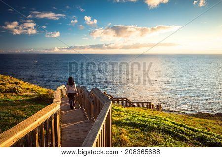 Woman walking down Hallett Cove boardwalk to enjoy sunset from beach South Australia
