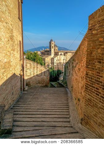 View from old street to Ducale Palace in Urbino city Marche Italy