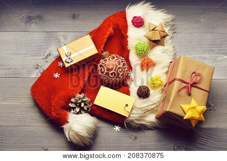 Colorful Christmas or New Year decoration of gifts with rose string yellow silver bow red ball Santa Claus red hat brown bow clews pine cone tag and snowflakes on vintage wooden background