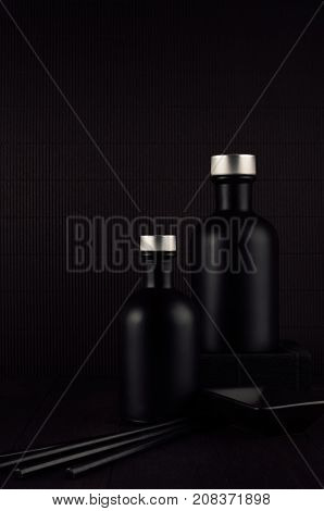 Noir exquisite home decor with blank black cosmetics bottles ceramics on dark wood board mock up. Dark black minimalist interior for advertising designers branding identity cover.