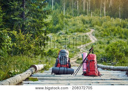Backpacks in the mountains on a wooden bridge across the river.