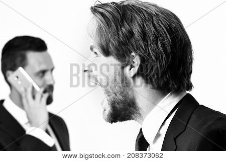Man Shouting To Busy Businessman Speaking On Phone