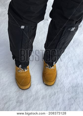 Black waterproof mountaineering snow cover, Gaiters covering black ski pants trousers over brown outdoor shoes on snow