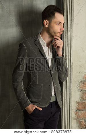 young handsome man with an unshaven face with a pensive look in a suit against a light wall background