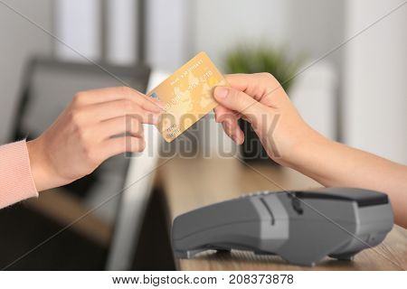 Young woman paying with credit card in hospital