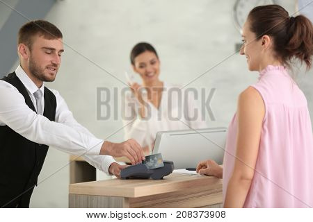 Woman paying for hotel room at reception