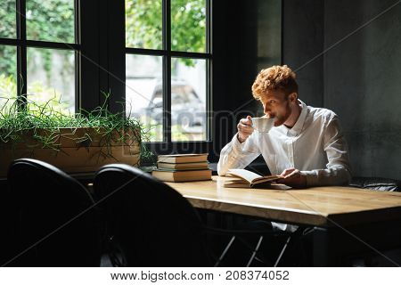 Photo of handsome readhead bearded man drinking coffee in city cafe, looking at large window