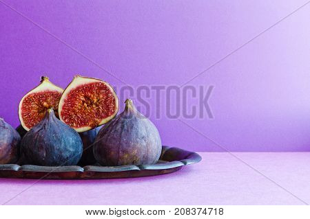 Bright still life organic fig fruits on an old tray, beautiful purple violet background. Selective focus photography, copy space.