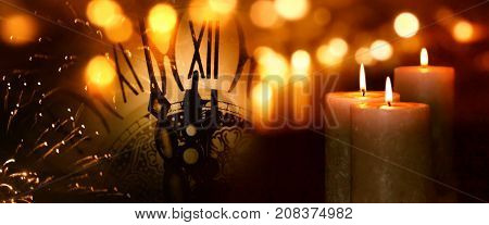 Burning candles with fireworks and golden bokeh at turn of the year