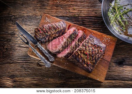 Beef Steak. Juicy Medium Rib Eye Steak Slices On Wooden Board With Fork And Knife Herbs Spices And S