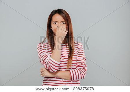 Portrait of a an upset disappointed asian woman crying and covering her face with hand isolated over gray background