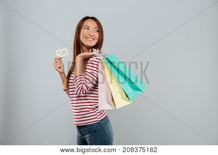 Side view of cheerful asian woman in sweater with credit card and packages while looking back over gray background