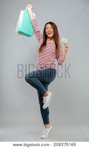 Full length image of Happy asian woman in sweater rejoice with credit card and packages over gray background