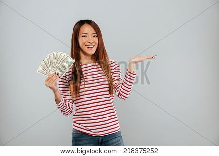 Smiling asian woman in sweater showing money and holding copyspace on the pound over gray background