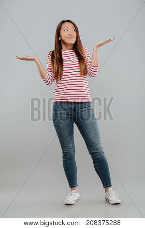 Full length portrait of a confused funny girl shrugging her shoulders and looking away at copy space isolated over gray background