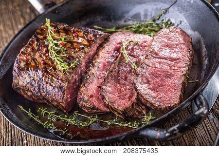 Beef Steak. Juicy Medium Rib Eye Steak Slices In Pan On Wooden Board With Fork And Knife Herbs Spice