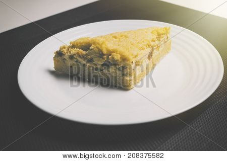 Peach pie on black and white background with sunlight from side. Yellow Peach pie on the table in kitchen. Peach pie with apricot.