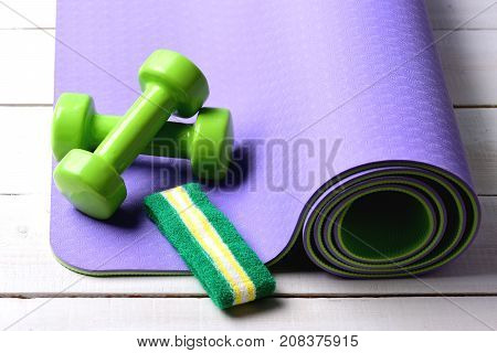 Shaping And Fitness. Barbells Near White And Green Head Band