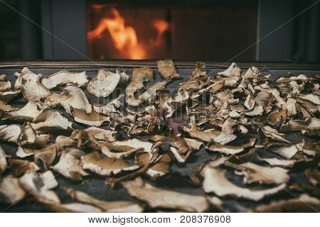 Dried mushrooms on the table on fireplace at background with fire. Storage of dried mushrooms. Mushrooms near fire in winter time. Heat of home (faded effect).  Mushrooms raw ingredient with flames.